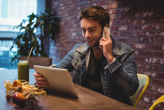 디지털 태블릿을 사용하는 동안 휴대 전화 통화하는 남자