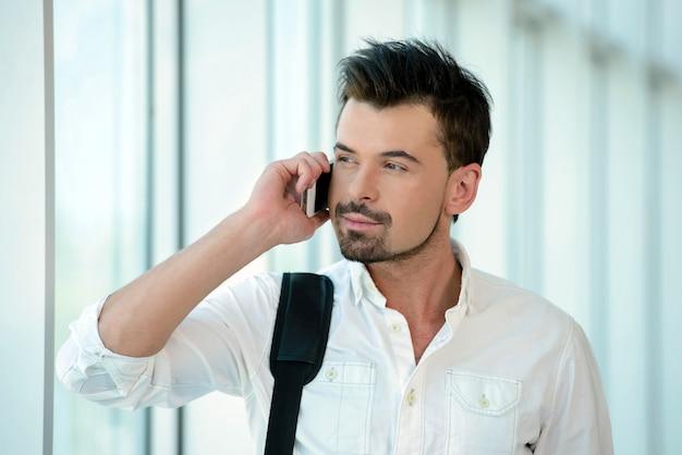 男は空港で歩いて電話旅行で話しています。