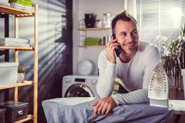 服をアイロンしながら電話で話している男性