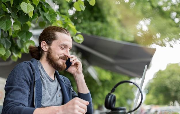 Человек разговаривает по телефону, находясь в городе