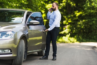 Man talking on smartphone opening car door