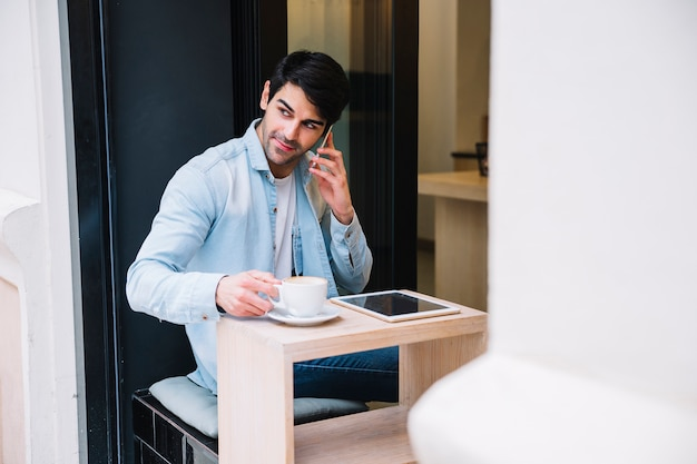Человек, говорить на смартфоне, сидя в кафе