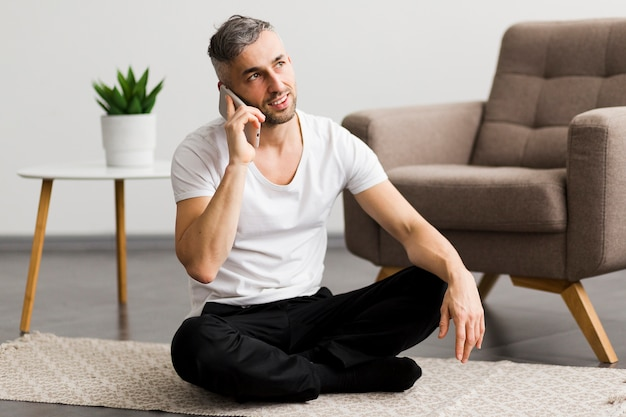 Мужчина разговаривает по телефону и сидит на полу