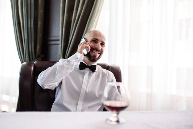 レストランで電話で話している男性。
