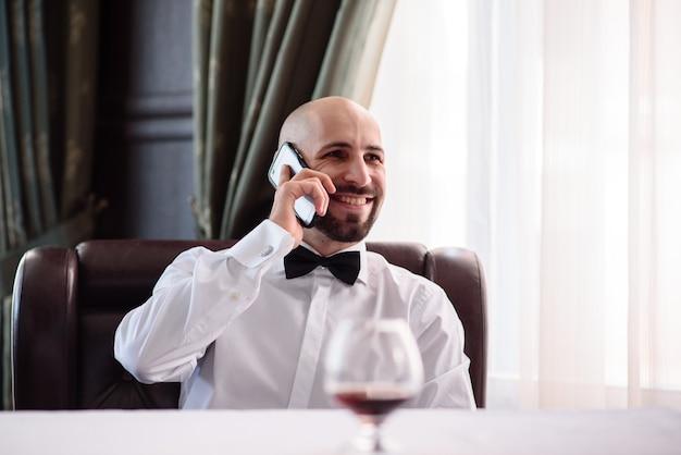 レストランで電話で話している男。