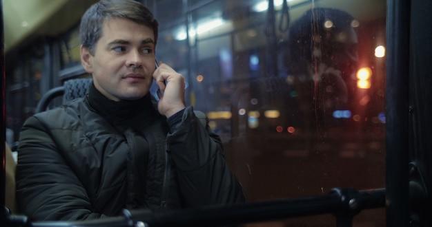 Человек разговаривает по телефону в автобусе