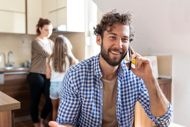 Человек разговаривает по телефону на кухне