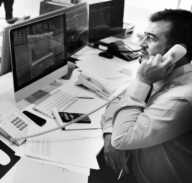 電話で話す男は、コンピュータ画面上の株式市場分析を見て