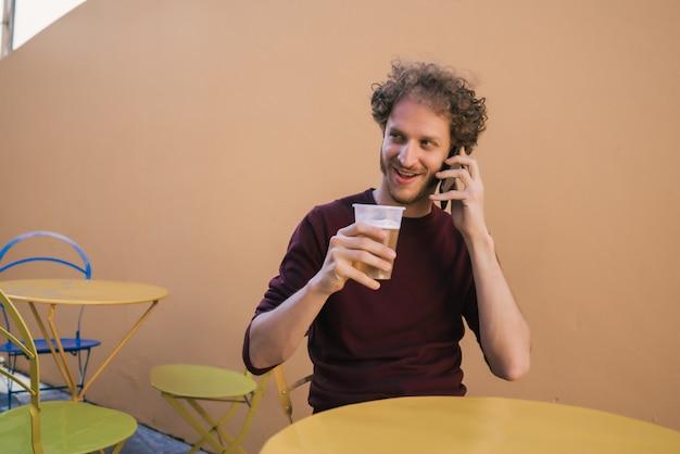ビールを飲みながら電話で話している男性。