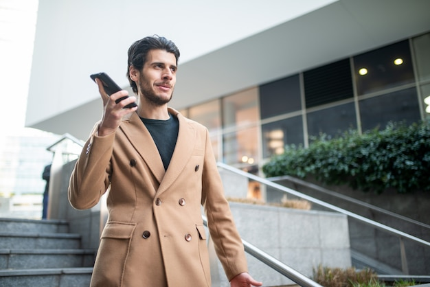 Человек разговаривает по телефону во время спуска по лестнице