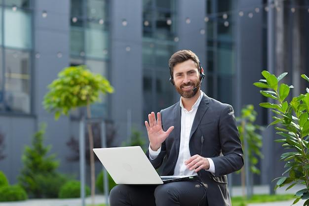 헤드셋으로 화상 통화를 하며 온라인으로 이야기하는 남자. 카메라, 회의 또는 회의를 멀리 보고 있는 남성. 초상화 학생 또는 교사 강의 훈련. 웹캠 보기