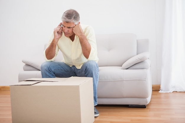 Man talking on phone looking at box