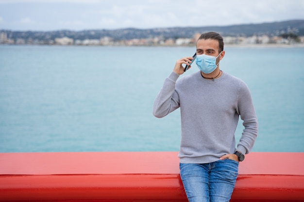 Man talking on the phone wearing a surgical mask