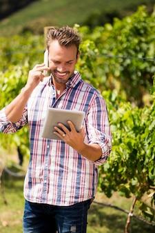 Man talking on phone while using tablet at vineyard