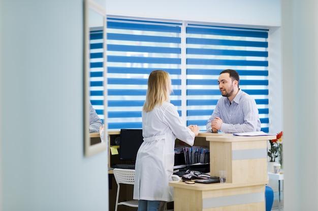 Мужчина разговаривает с женщиной-регистратором в больнице