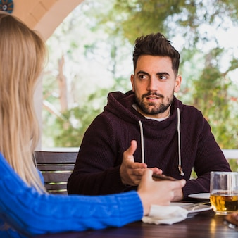 Man talking to woman at table outdoors