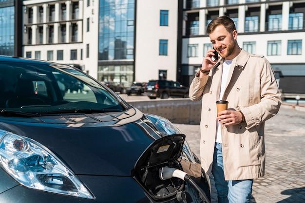 彼の車が駅で充電している間、男は電話で話します