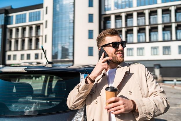 Мужчина разговаривает по телефону, пока его машина заряжается на станции