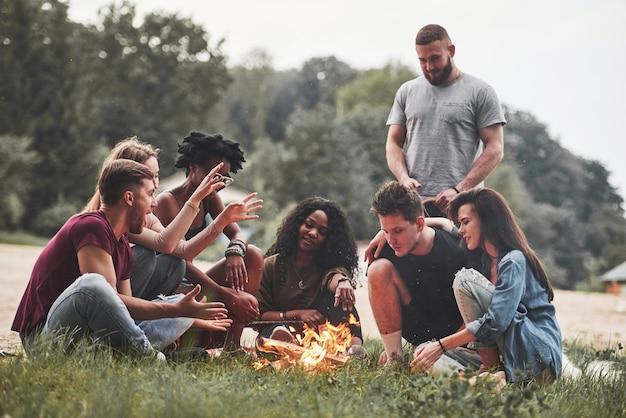 남자는 관심을 가지고 이야기합니다. 사람들의 그룹은 해변에서 피크닉을했습니다. 친구들은 주말에 즐겁게 지냅니다.