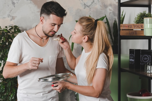 Man tasting the prepared mushroom by blonde young woman