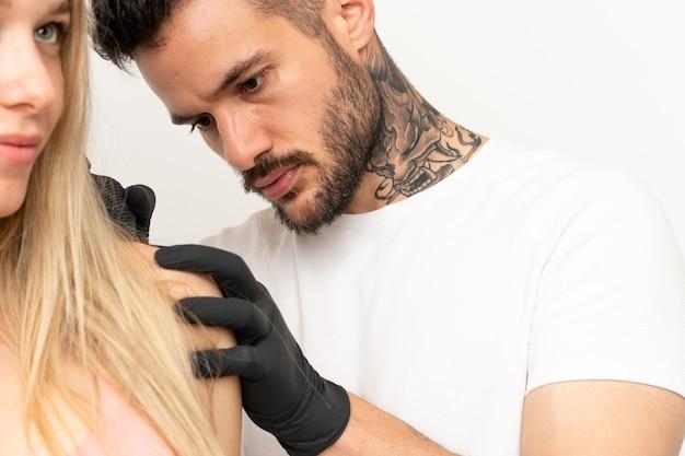 Мужчина татуирует девушку на изолированном фоне