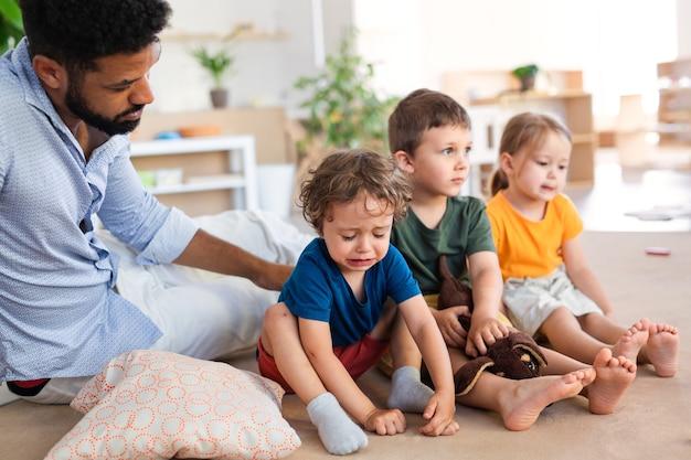 남자 교사는 교실에서 실내 보육원에서 우는 어린 소년을 위로합니다.
