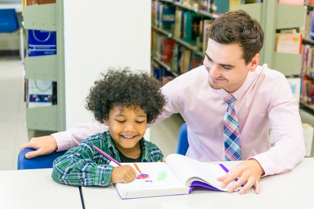 Man teacher and kid student learn with book at bookshelf background