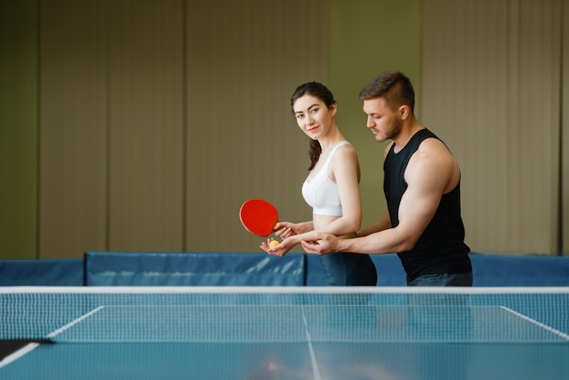 男性が女性に卓球をするように教え、室内でトレーニングする。