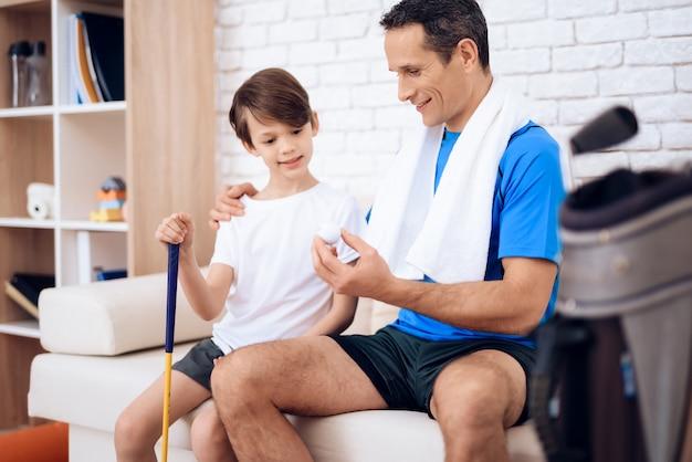 A man teaches his son to play golf.