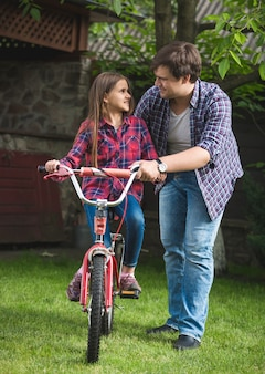 Man teaching cute girl how to ride a bicycle at park