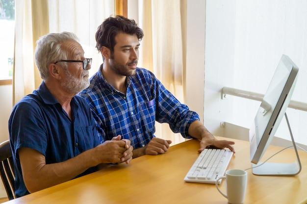 Человек учит пожилого человека пользоваться компьютером
