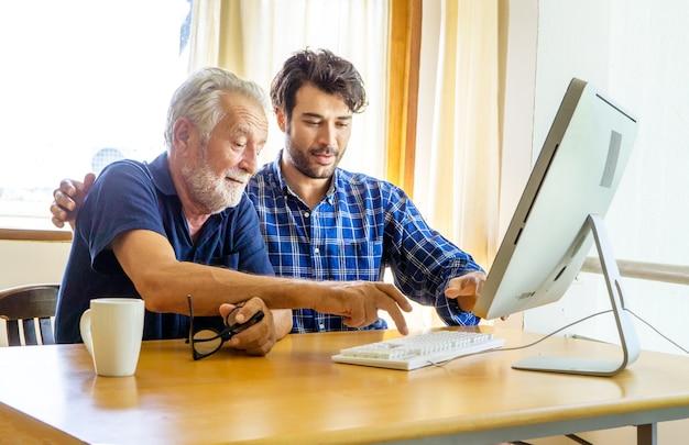 Мужчина учит пожилого мужчину пользоваться компьютером