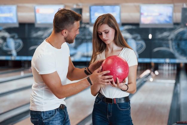 Uomo che insegna alla ragazza come tiene la palla e gioca a bowling nel club