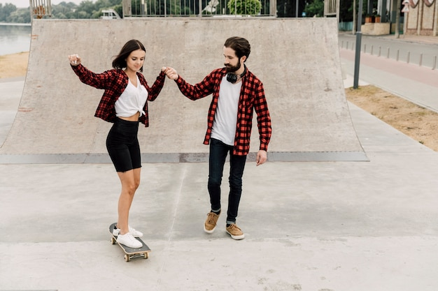 Man teaching girlfriend to ride a skateboard