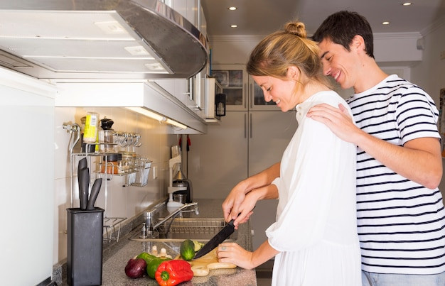 Man teaching her wife to cut vegetables with knife