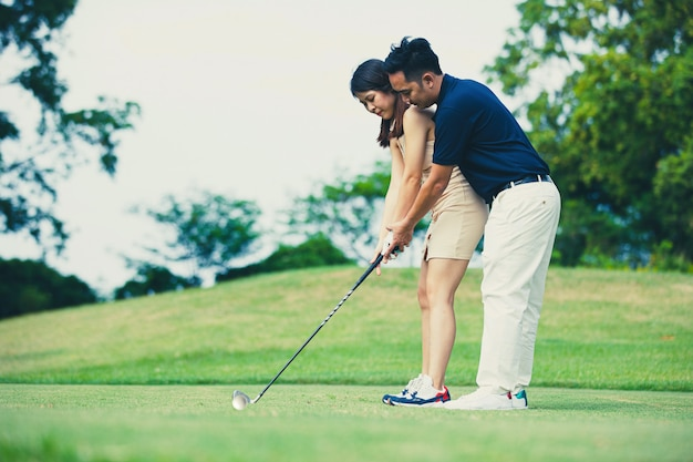 Man teaching woman to play golf while standing on field