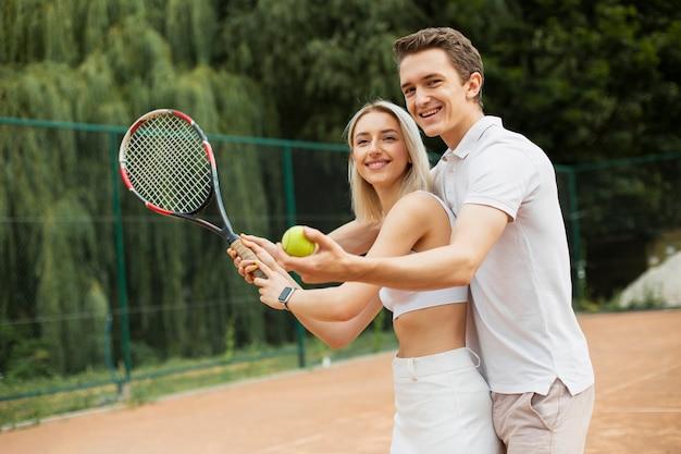 Man teaching woman to play tennis