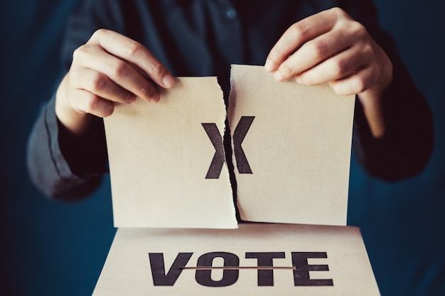 Man tear brown paper with x mark above vote box