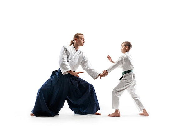 Man and teen boy fighting at aikido training in martial arts school. healthy lifestyle and sports concept. fighters in white kimono on white wall. karate men with concentrated faces in uniform.