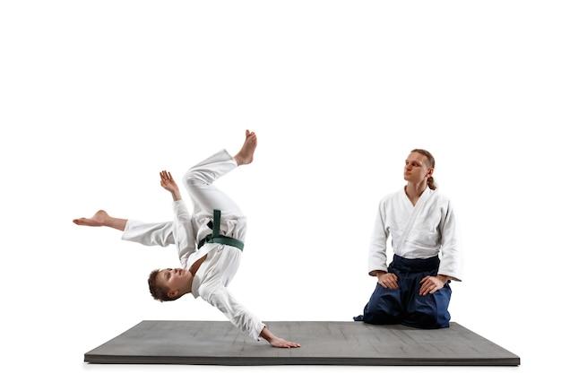 Uomo e ragazzo adolescente che combattono all'addestramento di aikido nella scuola di arti marziali. stile di vita sano e concetto di sport. fightrers in kimono bianco sulla parete bianca. uomini di karate con facce concentrate in uniforme.