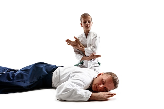 Man and teen boy fighting at aikido training in martial arts school. healthy lifestyle and sports concept. fightrers in white kimono on white wall. karate men with concentrated faces in uniform.
