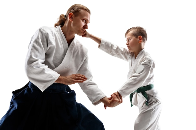 Man and teen boy fighting at aikido training in martial arts school. healthy lifestyle and sports concept. fightrers in white kimono on white wall