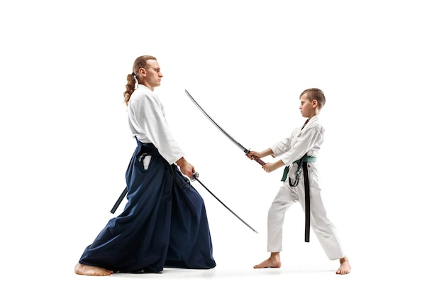 Man and teen boy fighting at aikido training in martial arts school. healthy lifestyle and sports concept.