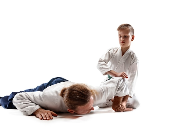 Man and teen boy fighting at aikido training in martial arts school