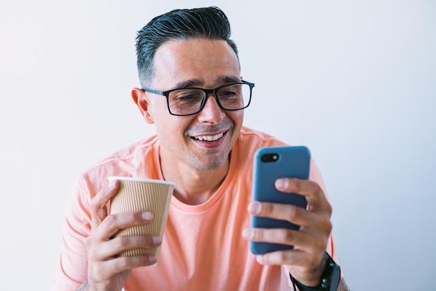 Человек, работающий удаленно из дома, смотрит в мобильный телефон за кофейным завтраком