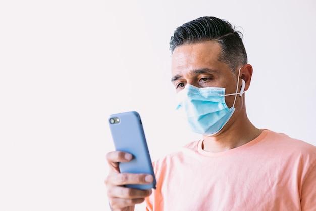 Мужчина удаленно работает из дома в хирургической маске, чтобы защитить себя от covid19