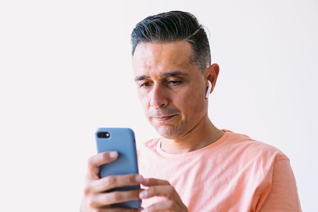 Человек, работающий удаленно из дома, в наушниках и глядя на мобильный телефон