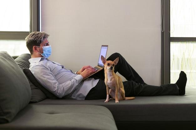 집에서 재택 근무를하고있는 남자, 노트북을 들고 그의 강아지 옆에있는 소파에 누워 있습니다.