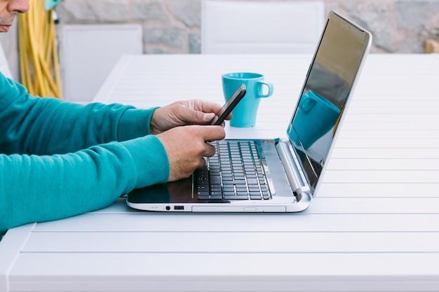 Человек удаленно работает со своим ноутбуком, глядя на свой мобильный телефон, в саду своего дома