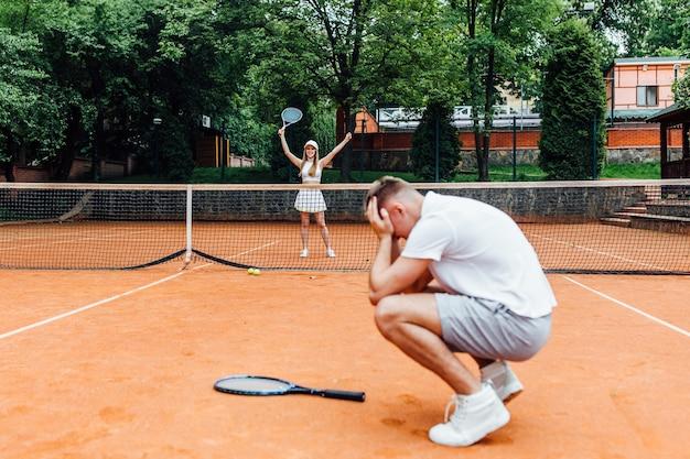 Uomo, insegnante di tennis, che mostra alla donna come si gioca lo sport di racchetta all'aperto.